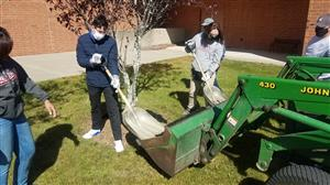 students putting mulch in a tree bed, after it was demonstrated to them by the ESASD Grounds personnel.